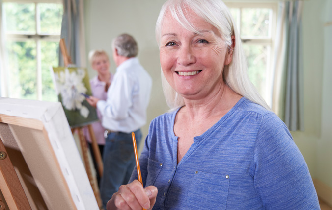 Woman smiling while in a painting class